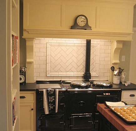 white subway tile with herringbone medallion behind a black Aga cooker - via Atticmag