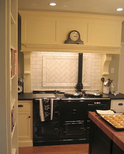 white subway tile with herringbone tile medallion behind a black Aga cooker - via Atticmag