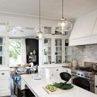 marble subway tile - range wall of a black and white kitchen with marble subway tiles by Jessica Helgerson - via Atticmag