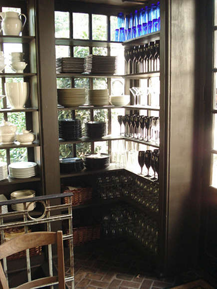 china room - shelves for china and glassware storage in front of windows in china storage room - Dungan Nequette via Atticmag