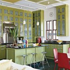 modern green kitchen with etched glass cabinet doors and red accents - Coastal Living via Atticmag