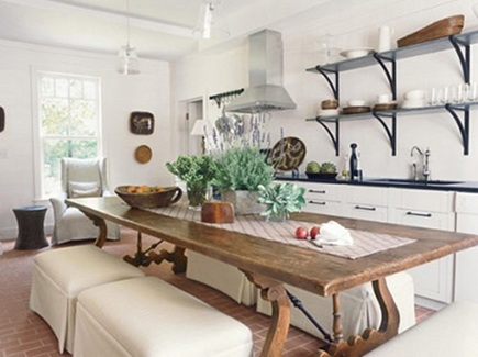 bright white kitchen cabinets with open shelving and antique wooden lyre base table in a guest house kitchen by Suzanne Kasler - Veranda via Atticmag