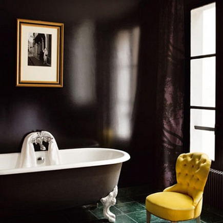 bathroom with painted black walls and black footed bathtub