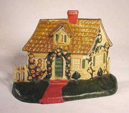 cottage doorstops - Hubley #211 and National's #150 cast-iron cottage doorstop with picket fence, ca 1940- Atticmag