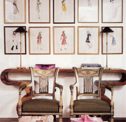 picture wall sets - wall of fashion prints over a console table - Domino via Atticmag