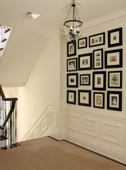 picture wall ideas - black framed pictures with white mats on a stairwell landing - Scott Yetman via Atticamg