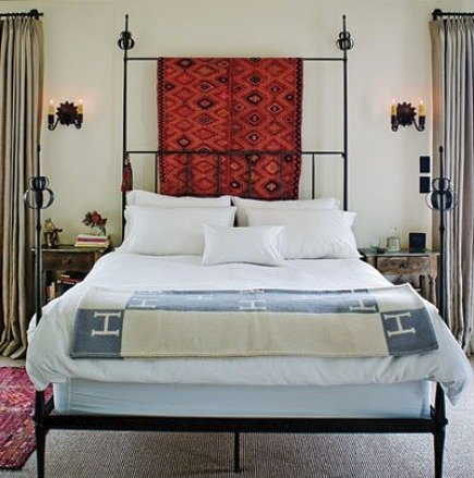 kilim rugs - Kilim rug draped over headboard - Sunset Magazine via Atticmag