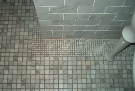 gray marble bathroom - floor detail of the one inch mosaic with small tile border - Atticmag