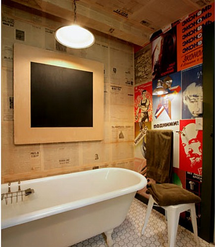 alternatives to wallpaper - bathroom walls covered with newspaper pages and vintage Soviet agitprop posters - via Atticmag