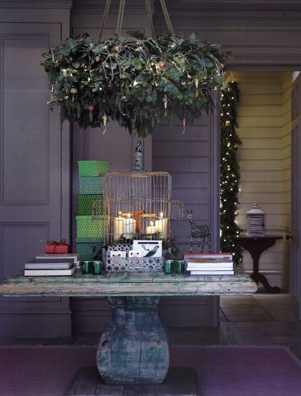 Christmas room - Christmas decorated chandelier wreath over an old table on the porch - House & Garden via Atticmag