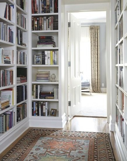 hallway rugs - bookcase lined hallway from Coburn Architecture and Interiors via Atticmag