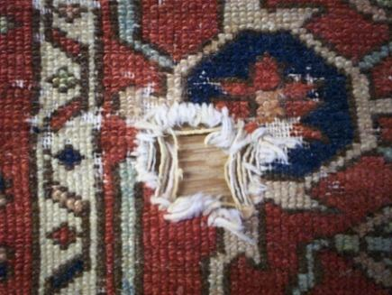rug buyer's checklist - hole caused by severe wear on an oriental carpet - Atticmag