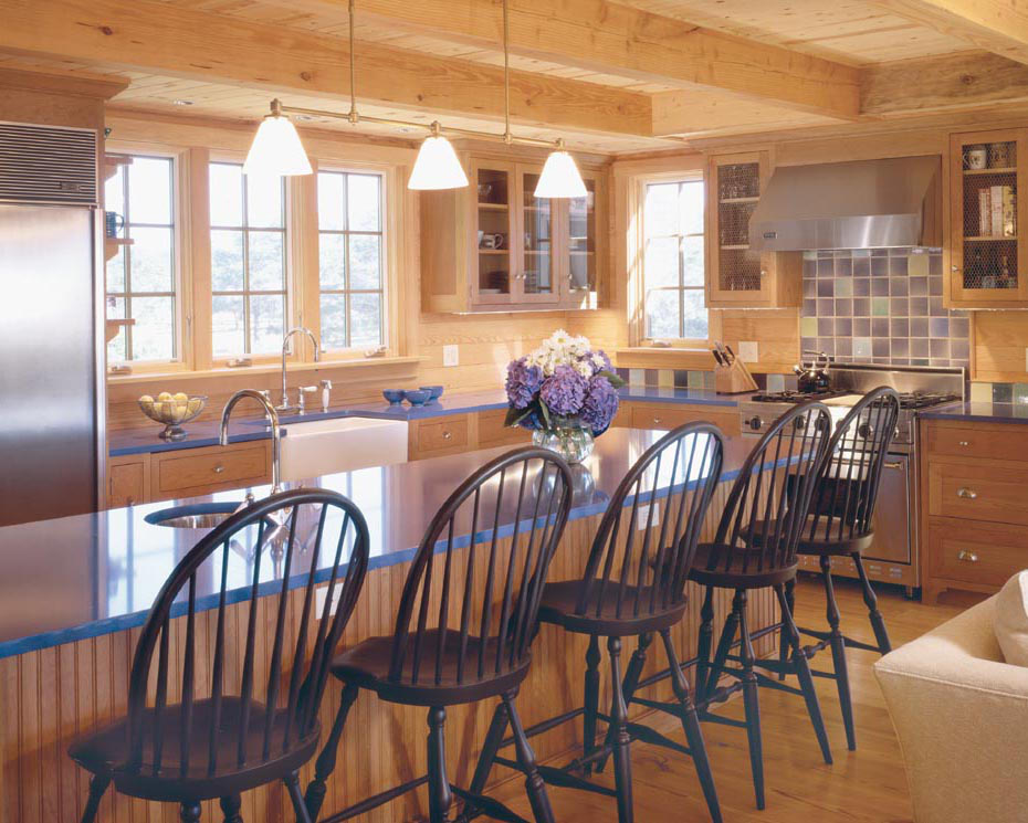 blue kitchen counters and purple tile backsplash with wood tone cabinets in a Massachusetts beach house kitchen - Hutker Architects via Atticmag