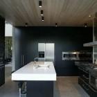 black lacquer kitchens - contemporary architectural kitchen with black cabinets and walls - Fearon Hay via Atticmag