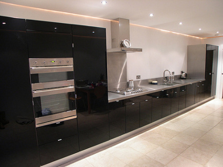 black lacquer kitchens - Ikea cabinet kitchen with stainless counters - via Atticmag