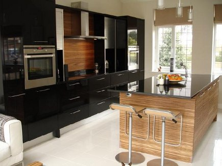 black lacquer kitchens - contemporary black and zebrawood kitchen with stainless tambour doors - via Atticmag