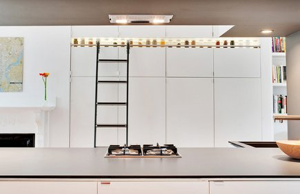 library ladder kitchen - two tiers of white Ikea pantry cabinets with a library ladder - dwell via atticmag
