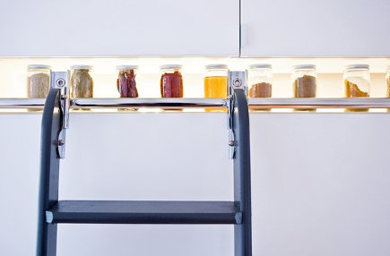 library ladder kitchen - close up of lighted space between cabinet and library ladder hardware - dwell via Atticmag