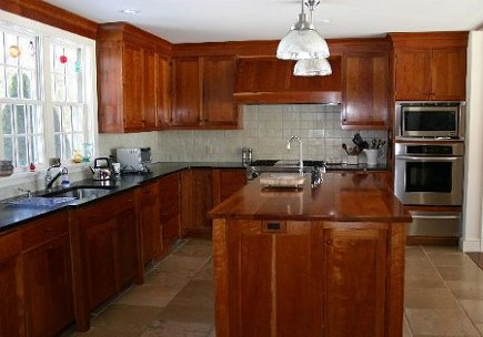 natural cherry cabinets in a kitchen with black granite counters - Atticmag