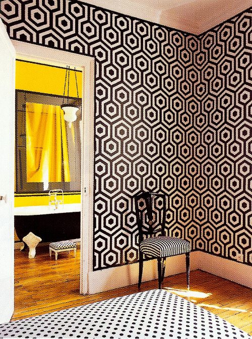 sunflower yellow bathroom seen from the master bedroom with black and white Op art walls and polka dot upholstery - WOI via Atticmag