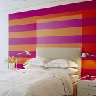 vivid horizontal stripe bedroom accent wall with white headboard - sheldon mindel via Atticmag