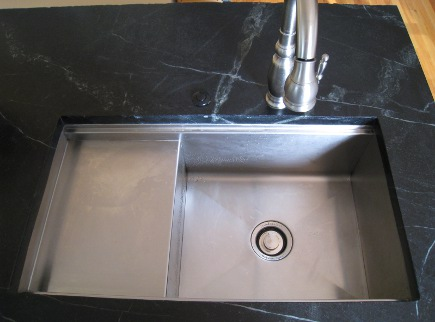 serious cook's kitchen - Kohler Stages sink in black and white kitchen island - Atticmag