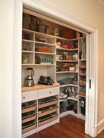 pantry with shelves and appliance hutch hidden by double pocket doors