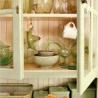 retro cottage kitchen - detail of glass-front cabinets in green kitchen - Country Living via Atticmag