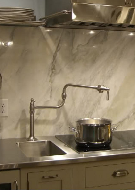 integrated trough sink adjacent to a cooktop in a stainless steel counter