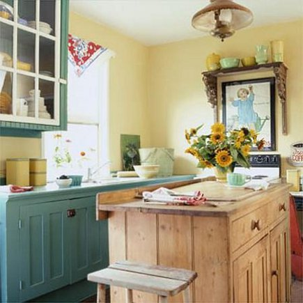 vintage look country cottage kitchen with yellow walls, a pine island and  teal cabinets -