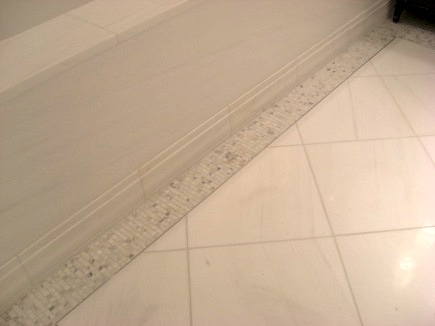 marble bathroom floors - detail of white polished marble show house floor with gray and white mosaic border - Atticmag