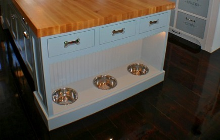 built ins for pets - custom island with inset dog bowls and dog bone shaped drawer pull cut outs - artisan kitchens via atticmag