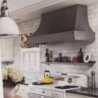 ccustom stainless steel range hood with scalloped trim over a vintage stove - Renovation Style via Atticmag