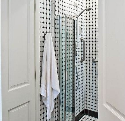 black and white hexagon tile shower hidden in a closet by architect L Craig Roberts