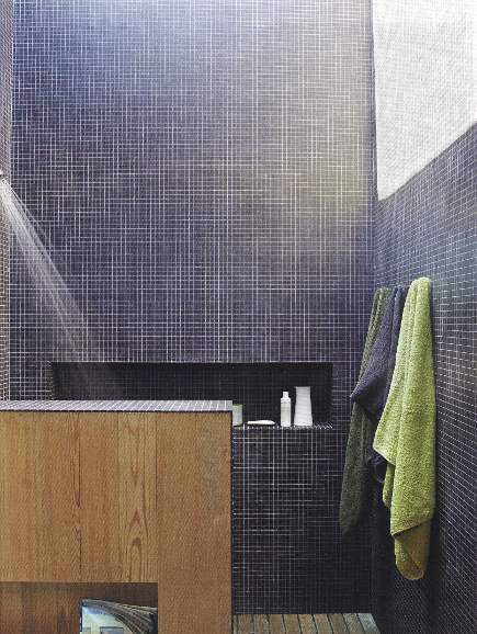 indigo blue color mosaic tiles in a modern bathroom with a lettuce green towel - Veranda via Atticmag