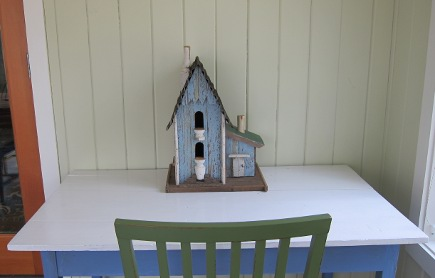 birdhouse on a blue-painted side table table in the sunroom - Atticmag