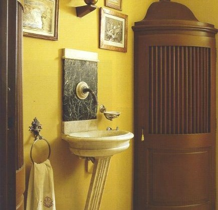 Henri Garelli's ochre powder room with curved antique corner cabinet - WOI via Atticmag