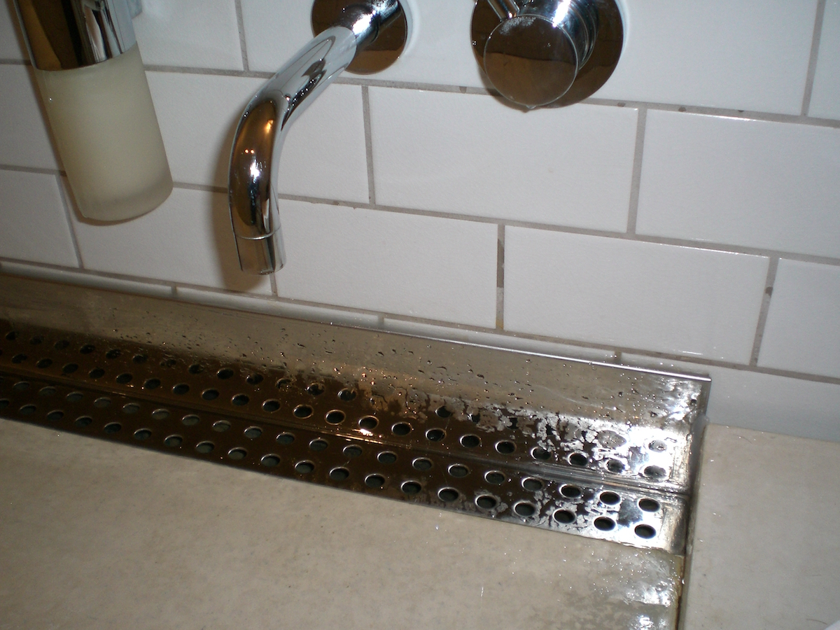 big bathroom sinks - details of oversize solid surface trough sink with linear drain and four faucets - Atticmag