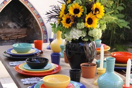glazed pottery - outdoor dining table set with colorful Bauer pottery dishes via Atticmag