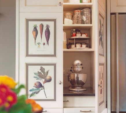 a baking center pantry is hidden behind kitchen cabinet doors inset with fruit and vegetable prints - The Sky Is The Limit Design via Atticmag