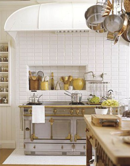 steel and brass La Cornue Chateau range on a Waterworks tile wall in a Victorian townhouse kitchen addition - House Beautiful via Atticmag