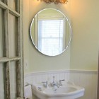 powder room mirror - country style powder room with Art Deco mirror from 1947 and a vintage eglomisé wall sconce - Atticmag