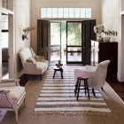 summer rugs - black and white striped dhurrie rug over sisal - House Beautiful via Atticmag