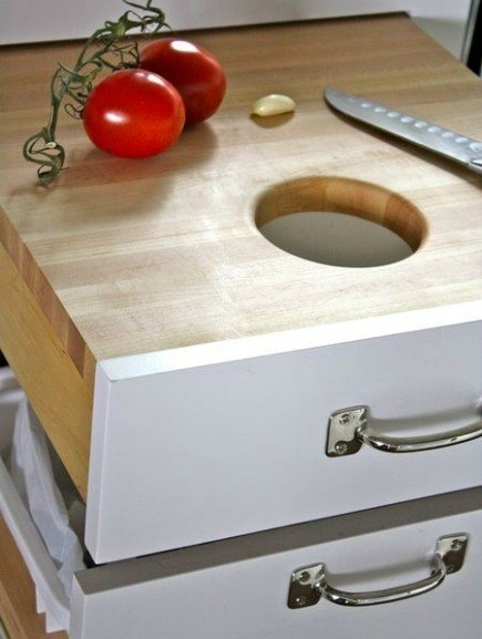kitchen cabinet ideas - cutting board pull-out drawer with trash chute over garbage bin - The Farm Chicks via ATticmag