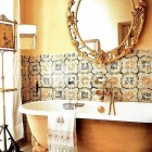 golden fantasy bath with painted clawfoot tub bathroom with intricate mirror and tile wainscot - The City Sage via Atticmag