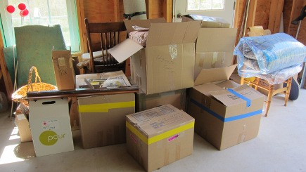 boxes of my yard sale items in Helen's garage, ready to be displayed - Atticmag