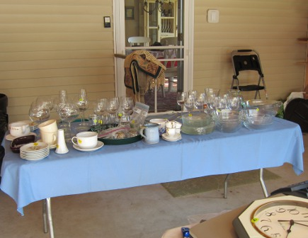yard sale table of glassware and specialty china at my house sale - Atticmag