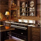 Lacanche ranges - black Sully range in a rustic wood-paneled kitchen - AD via Atticmag