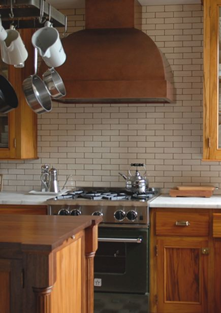 bottle green Blue Star range with custom copper hood and Walker Zanger Gramercy Park tile backplash in a renovated vintage gumwood cabinet kitchen - Atticmag