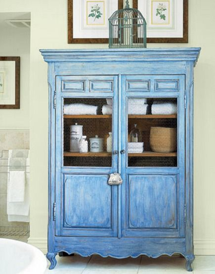 washed blue painted french style armoire with chicken wire inserts - Country Living via Atticmag